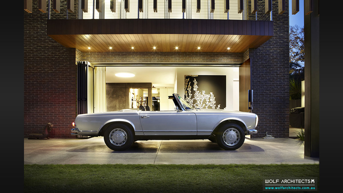 Silver Mercedes Pagoda framed in covered entry porch of Modern contemporary house by Wolf Architects