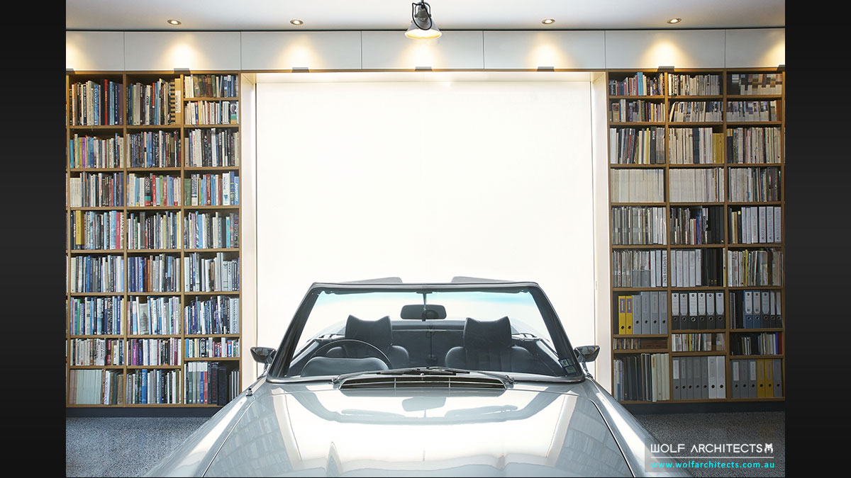 Wall of books with car in modern architects house by Wolf Architects