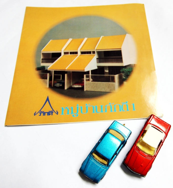 printed town house development brochure from the 70s and two matchbox cars