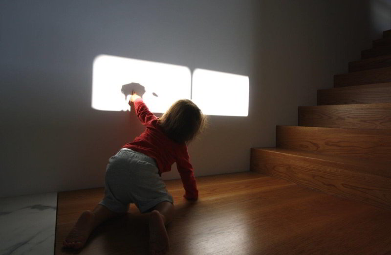 child playing with shadow cast on wall from star wars imperial walker